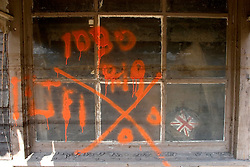 01 October, 05.  New Orleans, Louisiana. Lower 9th ward. Hurricane Katrina aftermath. <br /> The remnants of the lives of ordinary folks, now covered in mud as the flood waters recede.  Graffiti marks a window denoting no bodies recovered from the house with a British Union Jack visible through the glass.<br /> Photo; ©Charlie Varley/varleypix.com