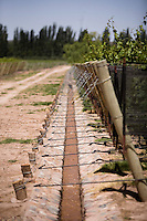 An open irrigation canal carrying water runs along Malbec grape vines at Bodega Melipal in the Luján de Cuyo area of Mendoza, Argentina.