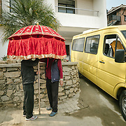 Second day of the wedding, during Puja ceremony, men waits for the bride with umbrellas.