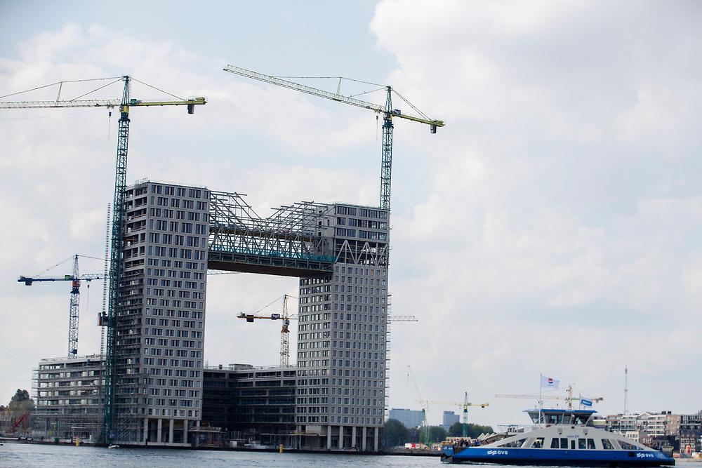 In Amsterdam vaart een veerboot van de GVB langs een woontoren in aanbouw met het duurste appartement van de hoofdstad.<br /> <br /> In Amsterdam a ferry passes the construction of a tower with the most expensive loft of the capital.