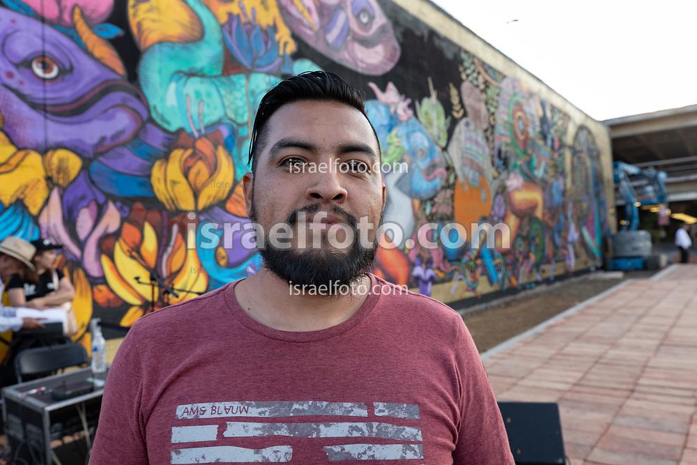 """El artista Israel Guerra, """"Spike"""", posa frente a un mural de su autoría en la Plaza de la Paz, Morelia, Michoacan / Artist Israel Guerra, aka Spike, poses in front of one of his works at Plaza de la Paz (Peace Square), in Morelia, Mexico."""