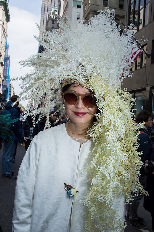 New York, NY, USA-27 March 2016. A woman in white, with a white hat with cascades of what looks like white-dyed fronds in the annual Easter Bonnet Parade and Festival.