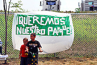 """USA, Chicago, August 25, 2009.   Children play next to a sign which reads """"We Want Our Park"""" outside the Celotex clean-up site, possible home for much-needed open space. The Little Village Environmental Justice Organization, headquartered in a predominantly Mexican-American neighborhood of Chicago, campaigns not only against pollution but for clean power, park facilities, urban agriculture, and restoring public transit. LVEJO's staff and volunteers make significant outreach and education efforts, especially for youth. Photo for an HOY feature story by Jay Dunn."""