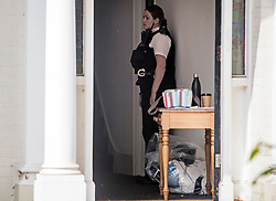 © Licensed to London News Pictures. 16/08/2020. London, UK. A police officer stands in the doorway of a property on Cumberland Park in Acton, West London where 10 year old boy was discovered dead after a woman handed herself in to police at a nearby station. . Photo credit: Ben Cawthra/LNP