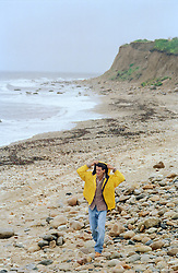 Man in a yellow jacket walking on the beach in Montauk, NY