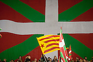 A Catalonian flag is waved in front of a big  Basque flag as people attend a tribute meeting to Basque politician Arnaldo Otegi, organized by Sortu pro-indpendence party, four days after he left prison. Donostia (Basque Country). March 5, 2016. Arnaldo Otegi is a politician, member of the Basque patriotic left movement, who was arrested in 2009, acused of trying to rebuild outlawed Batasuna pro-independence party, and was given a ten year sentence. In may 2012 Otegi's sentence was reduced to 6 1/2 years by the Spanish Supreme Court, as they decided he was not part of ETA. (Gari Garaialde / Bostok Photo)