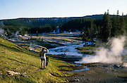 Hiker on trail watching geysers, Shoshone Geyser Basin, Yellowstone National Park, Wyoming..Subject photograph(s) are copyright Edward McCain. All rights are reserved except those specifically granted by Edward McCain in writing prior to publication...McCain Photography.211 S 4th Avenue.Tucson, AZ 85701-2103.(520) 623-1998.mobile: (520) 990-0999.fax: (520) 623-1190.http://www.mccainphoto.com.edward@mccainphoto.com