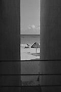 View between buildings of beach and umbrella in Playa del Carmen on the Yucatan Peninsula in Mexico (1984)