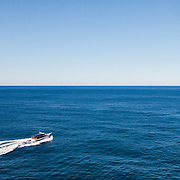 A tourist boat heading out on a clear blue day into an empty Adriatic Sea off the coast of Dubrovnik, Croatia.