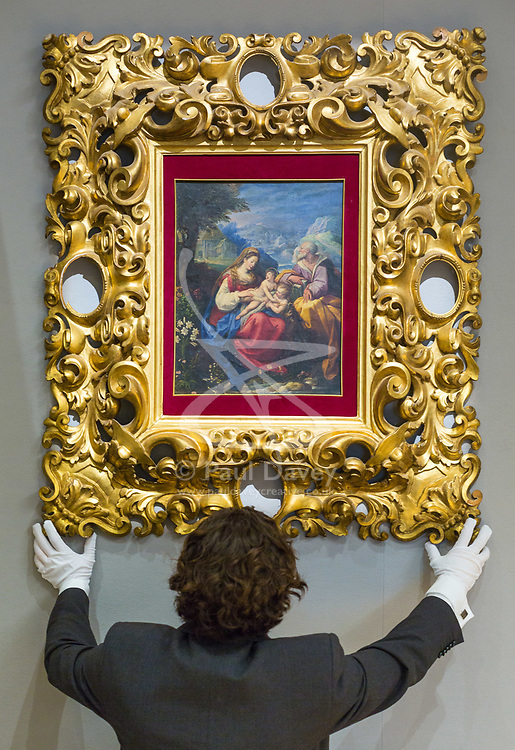 London, July 3rd 2017. A Bonhams gallery assistant hangs Jacopo Zucchi's The Holy Family with the Infant Saint John the Baptist in a carved 19th century Florentine frame, which is expected to fetch between £50-70,000 in their forthcoming Old Master Paintings sale.