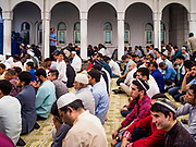 """15 JUNE 2018 - SEOUL, SOUTH KOREA: Men listen to the """"Khutbah,"""" or sermon, at Seoul Central Mosque on Eid al Fitr, the Muslim Holy Day that marks the end of the Holy Month of Ramadan. There are fewer than 100,000 Korean Muslims, but there is a large community of Muslim immigrants in South Korea, most in Seoul. Thousands of people attend Eid services at Seoul Central Mosque, the largest mosque in South Korea.   PHOTO BY JACK KURTZ"""