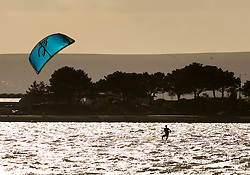 © Licensed to London News Pictures. 28/01/2016. Sandbanks, UK. A kite surfer speeds across Poole Harbour near Sandbanks in Dorset. Parts of the UK are enjoying a spell of sunshine after days of storms. Photo credit: Peter Macdiarmid/LNP