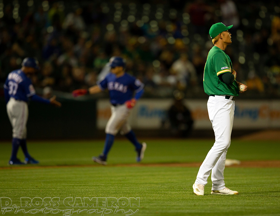 Jul 25, 2019; Oakland, CA, USA; Oakland Athletics pitcher Wei-Chung Wang, right, reacts to giving up a grand slam to Texas Rangers Danny Santana during the sixth inning of a baseball game at Oakland Coliseum. Mandatory Credit: D. Ross Cameron-USA TODAY Sports