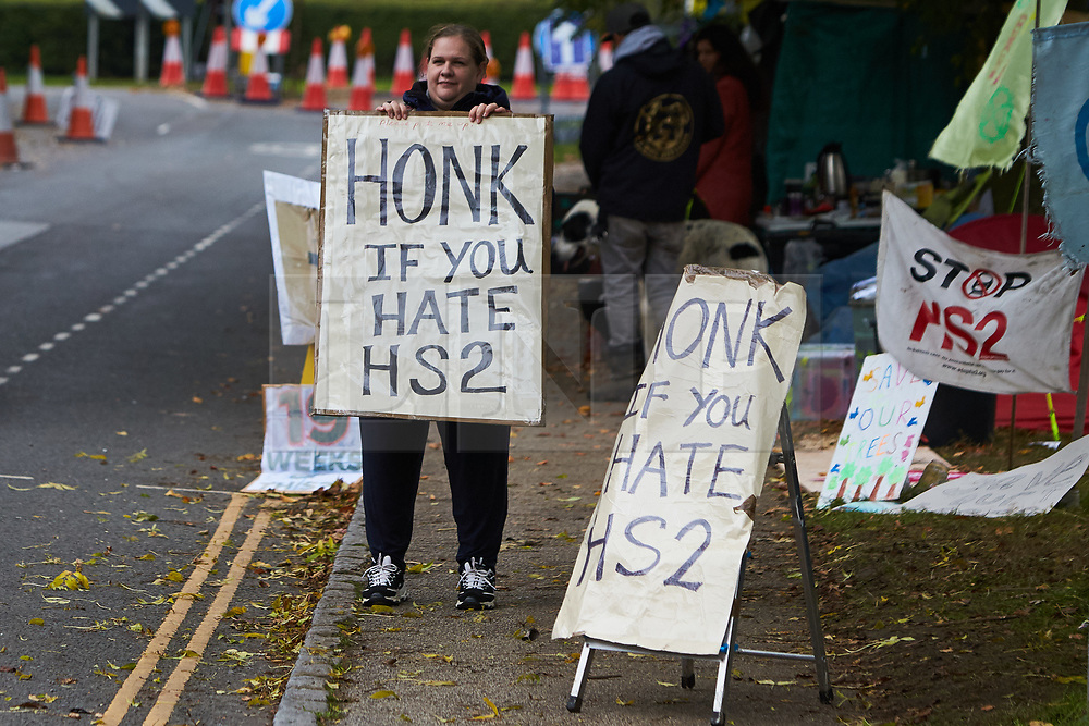© Licensed to London News Pictures. 23/10/2019. GREAT MISSENDEN, UK.  Enabling works to allow the construction of the HS2 railway continue despite the future of the project being reviewed. A number of mature trees were due to be felled last week to allow easier access for construction traffic but local residents and climate activists created a makeshift camp to prevent their destruction. In this picture: Protesters with a Honk If You Hate HS2 sign.  Photo credit: Cliff Hide/LNP