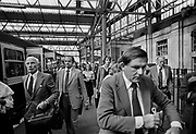 """Arrivals from the Crowded Guilford train 8.30am, Waterloo station. Most travellers on this Southern Region train would be middle class season ticket holders. British rail was the sole transport option for many rural areas. However, after """"The Beeching Report"""" many connections to villages were cut even before the wide spread of cars (for example in 1960s and 1970s) and public transport was nothing or based on coaches."""