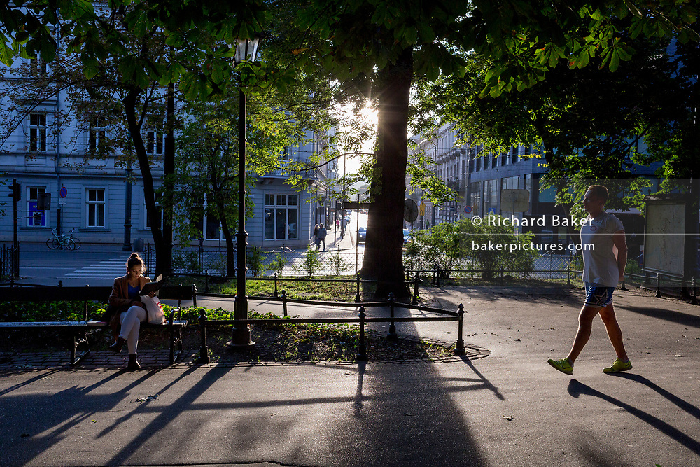 Seated on a park bench, as a young man approaches, a young woman reads a book in late afternoon sunshine, on 23rd September 2019, in Krakow, Malopolska, Poland.