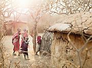 Maasai children gathered outside an Inkajijik, a typical Maasai house in Tipilit village near Amboseli