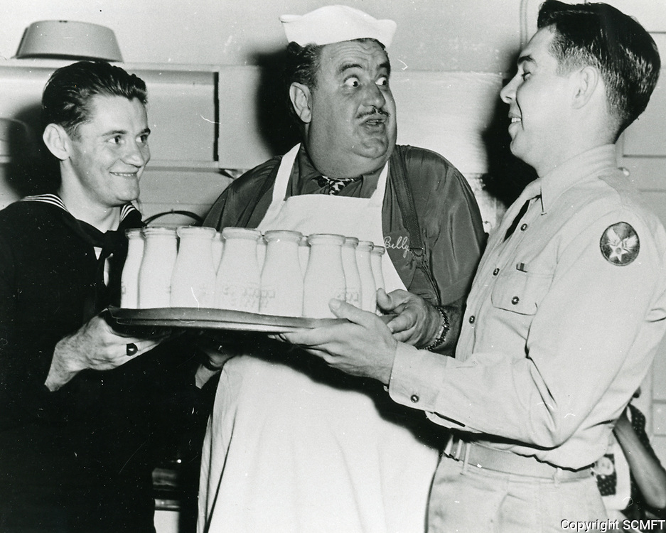 1944 Comedian, Billy Gilbert gets help carrying a tray of milk at the Hollywood Canteen.