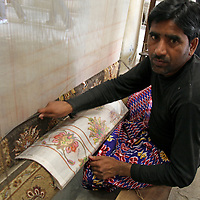 Asia, India, Jaipur. Weaver with pattern at loom working on a carpet.