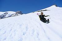 Woman sliding down Muir Snow Field Mt Rainier Washington USA&#xA;<br />