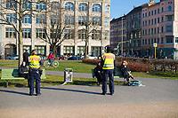 DEU, Deutschland, Germany, Berlin, 24.03.2020: Polizisten auf Streife kontrollieren Personen die auf dem Oranienplatz im Freien auf Parkbänken sitzen und dort lesen oder sich sonnen. Sie werden aufgefordert nach Hause zu gehen, da sich seit gestern niemand mehr ohne wichtigen Grund (z.B. einkaufen o. zur Arbeit gehen, allein Sport treiben) draussen aufhalten darf. Obwohl sie den Sicherheitsabstand von 1,5 m zueinander eingehalten haben, verstoßen sie somit gegen die Regeln, die zur Eindämmung der Ausbreitung des Corona-Virus von der Bundesregierung erlassen wurden. Auswirkungen der Pandemie, Coronavirus (Covid-19), Corona auf das öffentliche Leben in Berlin.