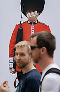 Shoppers walk beneath the image of a guardsman whose face has been obscured by an anti-vaxx message mocking pandemic face coverings, on Covid 'Freedom Day'. This date is what Prime Minister Boris Johnson's UK government has set as the end of strict Covid pandemic social distancing conditions with the end of mandatory face coverings in shops and public transport, on 19th July 2021, in London, England.