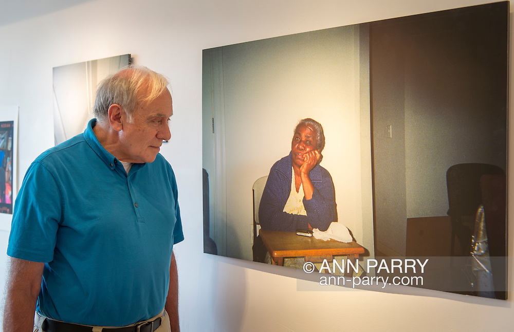 Huntington, New York, USA. August 1, 2015. GEORGE CARRANO looks at the photograph by Elodie Jean-Baptiste of her grandma at the Reception for Project Lives exhibition at fotofoto gallery. Over 200 residents throughout 15 New York Public Housing projects were given single use film cameras to photograph what's important to them in their world. The photography project was originated by Carrano and the book Project Lives was edited by Carrano, C. Davis and J. Fisher, with all royalties from its sale to be donated to resident programs at NYC Housing Authority. The gallery is on the Gold Coast of Long Island.