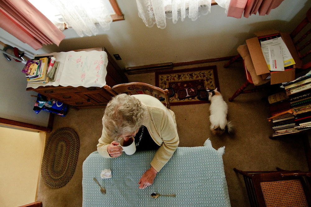 """(photo by Matt Roth).Friday, March 26, 2010.Pilesgrove, NJ..Corinne Bell sits down for a cup of tea and a Tastee Cake...Corinne Bell has lived in the home she and her husband built for 52 years. The widow now lives with three cats, Tiny, Cece, and Sheba, former strays who now call the split level on Main Street, Pilesgrove """"home,""""too. """"Somedays they're the only company I get,"""" says the 79-year-old New Jersey woman. Bell, like other New Jersey seniors who live on fixed incomes, are in danger of losing their homes because of the state's high property taxes -- the highest in the nation. """"I have too much stuff to move,"""" and worries about the future of her cats. In the past a social program called Senior Freeze alleviated a portion of the property taxes for those who qualified. The state's former governor changed the program's eligibility, but the state's new Republican Governor Christopher Christie said he would restore the rebates to those who lost them, but has yet to fully reinstate the program."""
