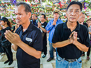 28 APRIL 2014 - BANGKOK, THAILAND: Men pray for Kamol Duangphasuk, 45, during the funeral for Kamol at Wat Samian Nari in Bangkok. Kamol was a popular poet who wrote under the pen name Mai Nueng Kor Kunthee. Kamol had been writing since the 1980s and was an outspoken critic of the 2006 coup that deposed Thaksin Shinawatra. After the 2010 military crackdown against the Red Shirts he went into temporary self imposed exile fearing for his safety. After he returned to Thailand he organized weekly protests against Thailand's Lese Majeste laws, which he said were being used to stifle dissent. Kamol was shot and murdered on April 23. The assailants are still at large but the murder is thought to be political.     PHOTO BY JACK KURTZ