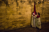 Two member of a cofradia along the wall of the Mezquita. Young girls with baskets bring water to satisfy the thirst of the members of the parade. Every procession of the Holy Week in Cordoba leaves its neighbourhood to head to the Cathedral. Andalusia, Spain