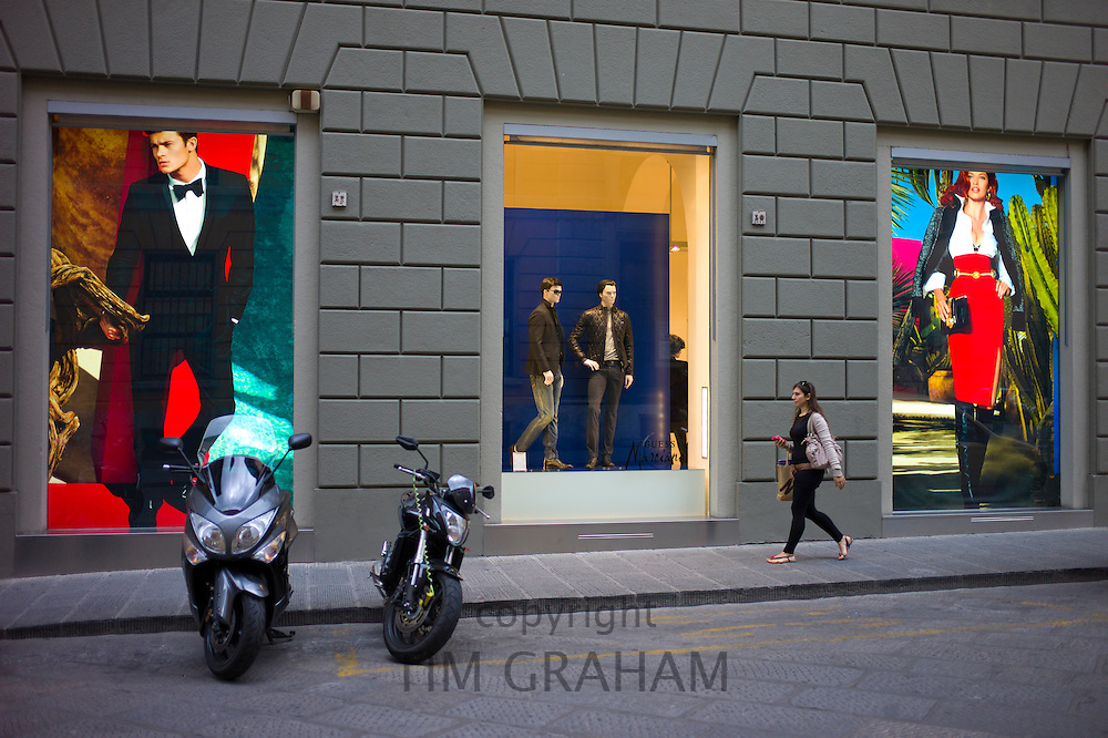 Stylish Italian woman walks past fashion displays of Guess Marciano casuals in Via de Pecori in Florence,Tuscany, Italy