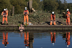 HS2 security guards monitor an anti-HS2 activist standing in the Grand Union Canal to halt tree felling works alongside HOAC lake in connection with the HS2 high-speed rail link on 21 September 2020 in Harefield, United Kingdom. Anti-HS2 activists continue to try to prevent or delay works for the controversial £106bn HS2 high-speed rail link on environmental and cost grounds from a series of protection camps based along the route of the line between London and Birmingham.