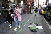 People more fortunate pass a homeless sleeping bag on the pavement near Old Street in London, England, United Kingdom.