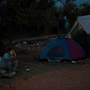 A refugee checking his mobile phone outside his tent in Kara Tempe camp.