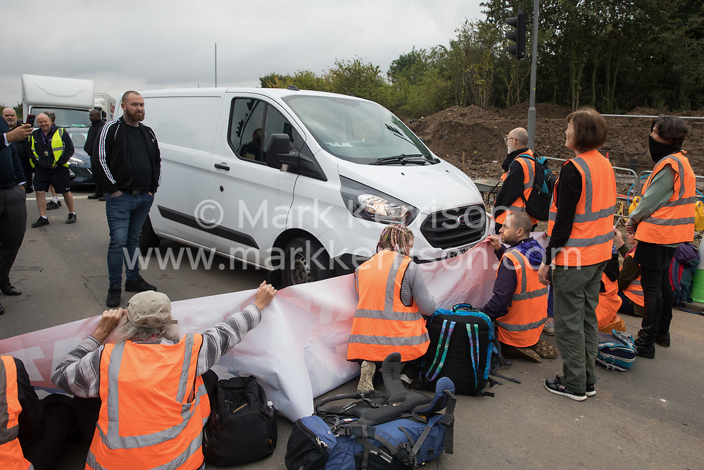 Enfield, UK. 15th September, 2021. A white van is driven towards Insulate Britain climate activists blocking a slip road from the M25 at Junction 25 as part of a campaign intended to push the UK government to make significant legislative change to start lowering emissions. The activists, who wrote to Prime Minister Boris Johnson on 13th August, are demanding that the government immediately promises both to fully fund and ensure the insulation of all social housing in Britain by 2025 and to produce within four months a legally binding national plan to fully fund and ensure the full low-energy and low-carbon whole-house retrofit, with no externalised costs, of all homes in Britain by 2030 as part of a just transition to full decarbonisation of all parts of society and the economy.