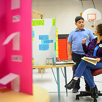 112113  Adron Gardner/Independent<br /> <br /> Fifth-grade-student Zack Byman, left, and science fair judge Gillian Mair talk about the Apatosaurus as Mair scores a dinosaur display made by Amber John at the Red Rock Elementary Science Fair in Gallup Thursday.