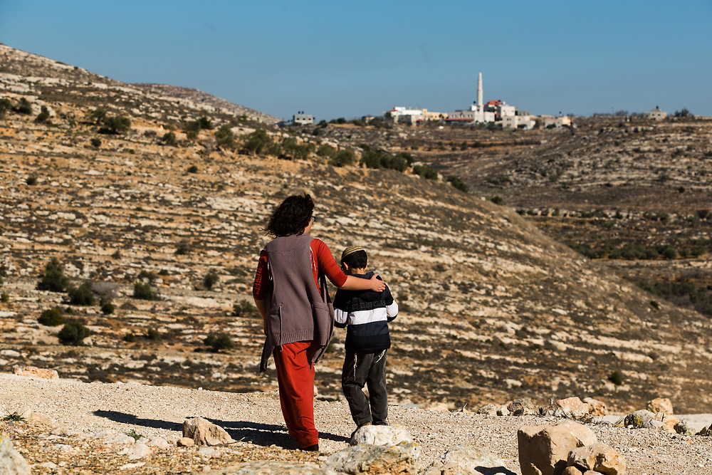 A Palestinian village is seen on a hilltop in the background as Israelis visit the archaeological park of Ancient Shiloh, which is located at the entrance to the modern Jewish settlement of Shiloh, south of the Palestinian West Bank town of Nablus, on January 1, 2017. Shiloh was the religious capital of Israel, an assembly place for the people of Israel and a center of worship before the first temple was built in Jerusalem. Its sacred area housed the Ark of Covenant.