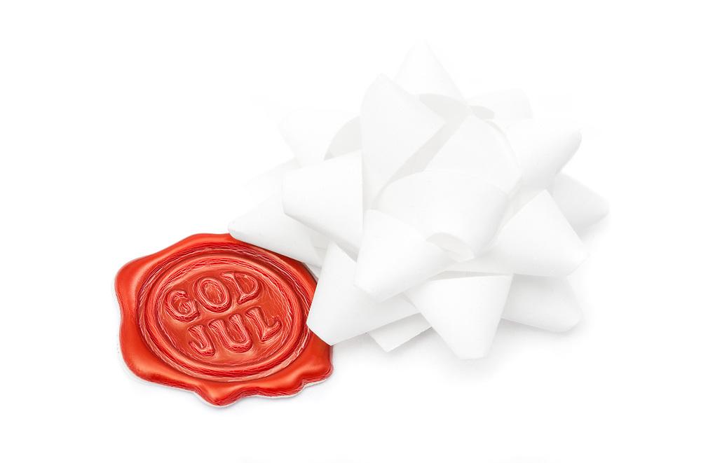 Rødt lakkstempel med «God Jul»-hilsen flankert av hvit gaverosett, på hvit bakgrunn.