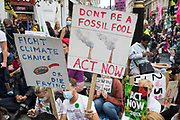 Environmental activists from Extinction Rebellion assemble around a giant table used to block roads in the Covent Garden area during the first day of Impossible Rebellion protests on 23rd August 2021 in London, United Kingdom. Extinction Rebellion are calling on the UK government to cease all new fossil fuel investment with immediate effect.