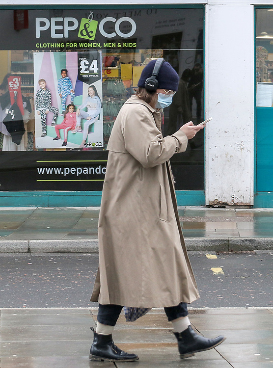21st February, Cheltenham, England. A girl wearing a mask walks past Poundland in the town centre which remains open as part of the lockdown restrictions.