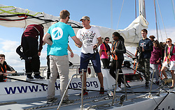 Simon Le Bon (centre) arrives back at Gunwharf Quays on board a 72 foot Challenger yacht after racing in the Solent with members of the Tall Ships Youth Trust team.