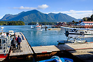 Passengers wait to board a water taxi while a floatplane returns to the dock in the calm harbour of Tofino, British Columbia