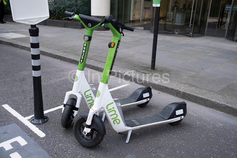 Two Lime eScooters at an eScooter parking bay on 11th August 2021 in London, United Kingdom. A scooter-sharing system is a shared transport service in which electric motorized scooters, also referred to as e-scooters, are made available to use for short-term rentals. E-scooters are typically dockless, meaning that they do not have a fixed home location and are dropped off and picked up from certain locations in the service area.