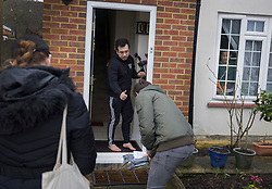 © Licensed to London News Pictures. 18/02/2021. Woking, UK. Volunteers deliver Covid-19 home testing kits to householders in Maybury near Woking, Surrey. This is the third surge testing operation in Surrey after a case of the South African variant of the Covid-19 virus was found locally. Photo credit: Peter Macdiarmid/LNP
