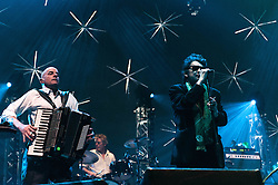 © Licensed to London News Pictures. 20/12/2012. London, UK.   James Fearnley (left), Andrew Ranken (centre) and Shane MacGowan (right) of The Pogues performing live at The O2 Arena for their only UK live date of 2012 as part of their 30th Anniversary Tour.  The Pogues are a Celtic punk band from London, formed in 1982 and fronted by Shane MacGowan.  Members include Shane MacGowan (vocals, guitar, banjo, bodhrán),.Spider Stacy (vocals, tin whistle), Jem Finer (banjo, mandola, saxophone, hurdy-gurdy, guitar, vocals), Andrew Ranken (drums, percussion, harmonica, vocals), .James Fearnley (accordion, mandolin, piano, guitar), .Philip Chevron (guitar, vocals),  Darryl Hunt (bass guitar),.Terry Woods (mandolin, cittern, concertina, guitar, vocals).     Photo credit : Richard Isaac/LNP