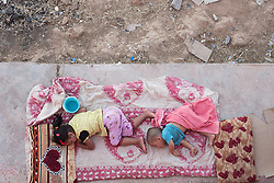 © Licensed to London News Pictures. 25/06/2014. Khanaqin, Iraq. Five year old Aya (L) and one year old Bilal Madi, Iraqi refugees from the front line town of Jalawla, sleep in the shade of a barn at the Bahari Taza refugee camp in Iraq. Aya and Bilal escaped the town with their Tukman family after fighting commenced between ISIS and Kurdish Peshmerga forces. Located on the outskirts of Khanaqin, a town just 20 minutes from the front-line of the battle with ISIS insurgents, the Bahari Taza refugee camp, and its satellite camps, now house around 600 families from southern Iraq. Built by the local village leader to meet the influx of refugees from nearby Jalawla and Saidia, where intense fighting is still taking place.Turkman, Arab and Kurd, both Sunni and Shia, all live together in tents, barns and unfinished buildings waiting for the conflict to end. Photo credit: Matt Cetti-Roberts/LNP