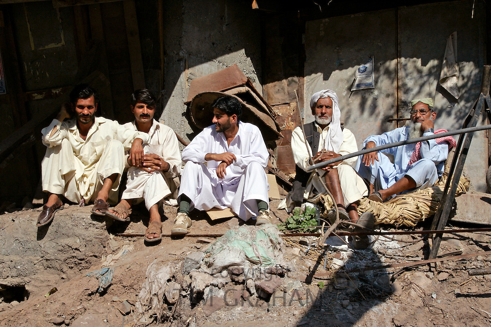 Pakistani men sit together in earthquake devastated village of Pattika, Pakistan