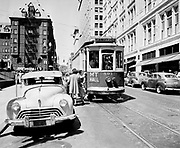 "deLay480700-1The Morrison street trolley going to Mt. Tabor is picking up passengers in front of the Pioneer Courthouse. The Portland Hotel is in the background. 1948 license plates on all cars in photo. Trolley 591. Published August 1, 1948 pg. 29 ""Dangerous. Center of street loading requirements of streetcars is a constant danger to passengers, traffic engineers point out. This photograph demonstrates possibility of cars striking passengers."""