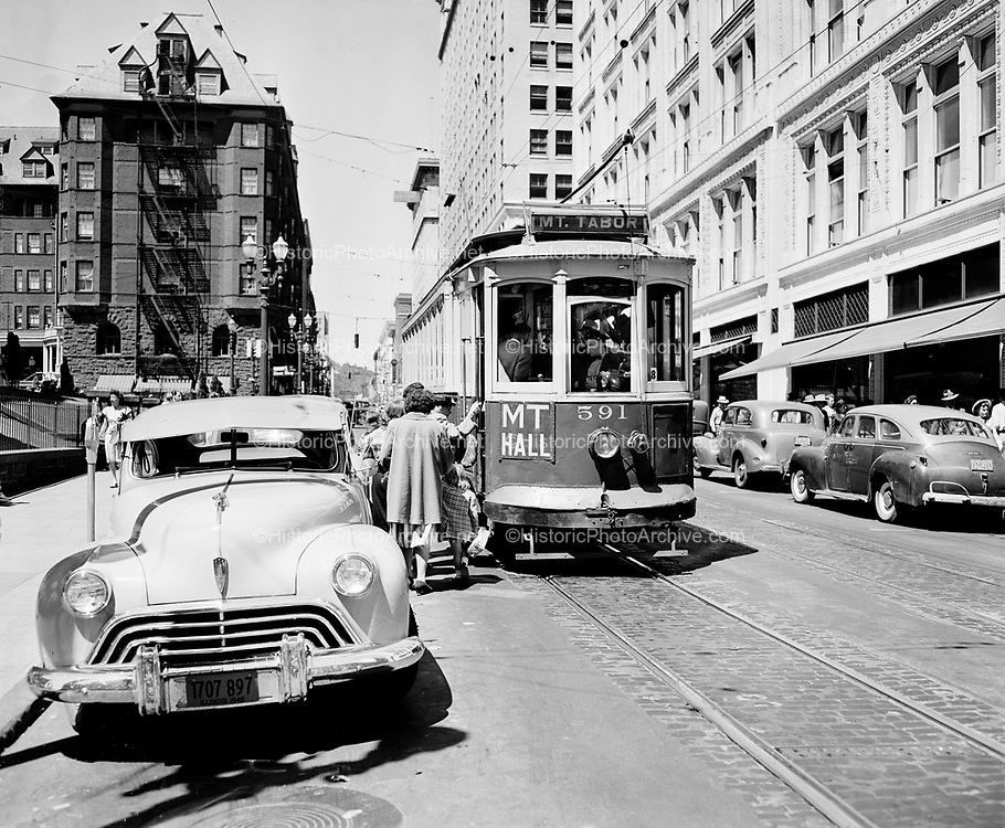 """deLay480700-1The Morrison street trolley going to Mt. Tabor is picking up passengers in front of the Pioneer Courthouse. The Portland Hotel is in the background. 1948 license plates on all cars in photo. Trolley 591. Published August 1, 1948 pg. 29 """"Dangerous. Center of street loading requirements of streetcars is a constant danger to passengers, traffic engineers point out. This photograph demonstrates possibility of cars striking passengers."""""""