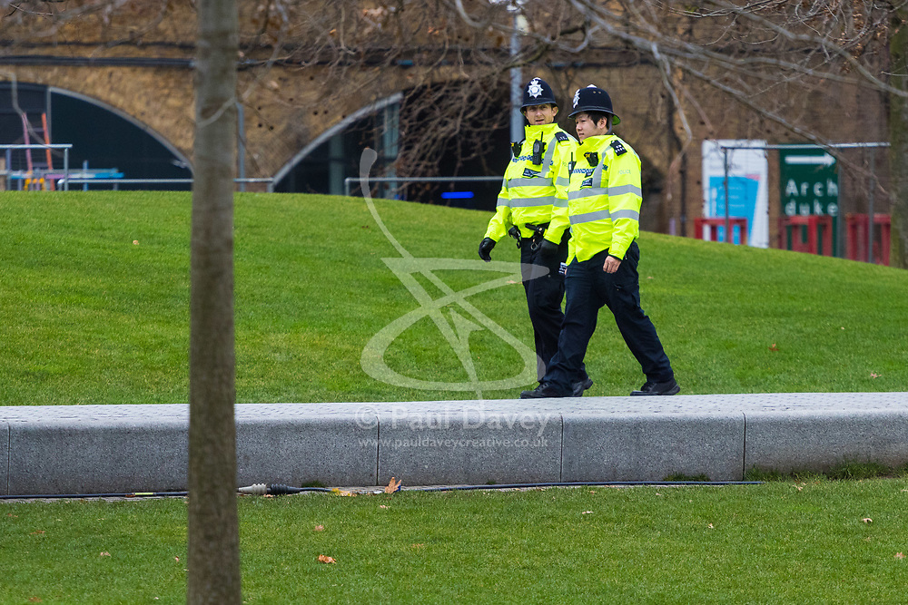 London, December 31 2017. Police in high visibility jackets and numerous anti-terrorism and crowd control measures are in place in the capital ahead of the New Year's Eve fireworks and revelry in central London. PICTURED: Two police officers patrol Southbank gardens. © SWNS